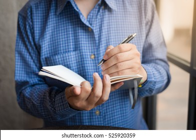 Adult freelance businessman writing on small notebook in cafe on weekend morning. Freelance businessman lifestyle on weekend concept