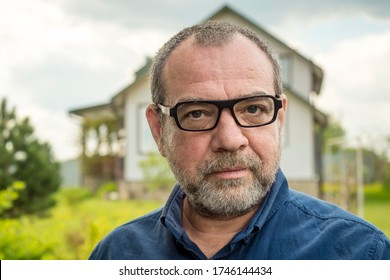 Adult friendly man with glasses close-up face near his country house
