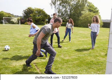 Adult friends having fun with a football on a playing field