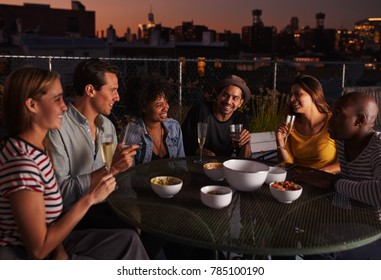 Adult friends talking around a table on a rooftop, evening