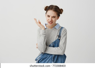 Adult girl 30s gesturing skeptically expressing disagreement with facial expressions. Female employer with childish hairstyle being disappointed with final results. Reactions, attitude concept