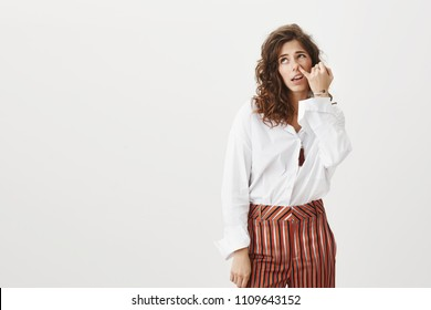 Adult girl do not want making any effort and work. Careless dumb funny woman with curly hair in stylish clothes, gazing up at camera while picking in nose with pinky, being indifferent and stupid