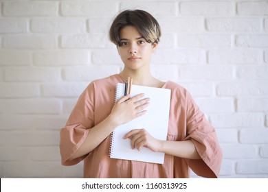 adult girl draws on paper pencils / portrait of a beautiful young female student, art school education, concept of art education