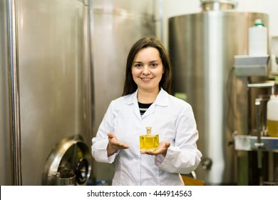 Adult girl posing with bottle of essence at perfume oil industry