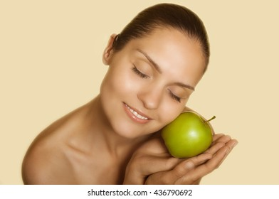 adult girl pressed green apple to her cheek