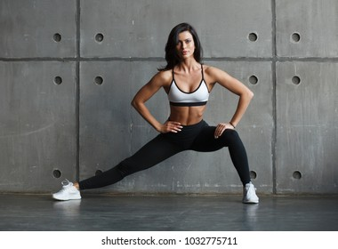 adult girl in sportswear doing stretching exercise in gym