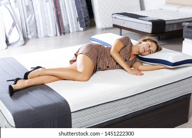 adult girl testing quality of new mattress for bed in salon