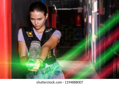 Adult girl in waistcoat holding colored laser guns and took aim during laser tag game in labyrinth