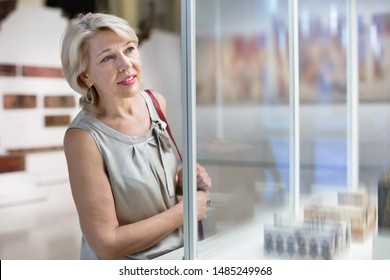 Adult glad cheerful  female looking at artwork copper exhibit in the gallery indoors