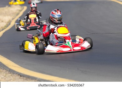 Adult Go Kart Racers on Track.  Four drivers are coming into a turn competing for position.