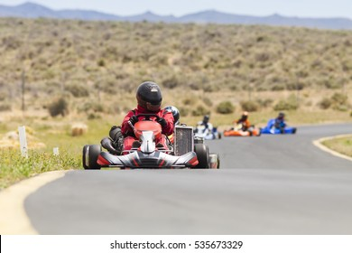 Adult Go Kart Racers on Track.  Five carts in a row heading into turn.
