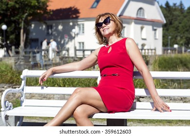 Adult good-looking woman sunbathing on the bench
