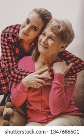Adult granddaughter embrancing grandmother, visiting at home.