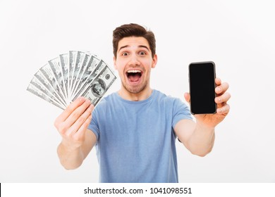 Adult guy with bristle and dark hair demonstrating his money prize and copyspace screen of smartphone isolated over white wall