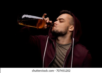 An adult guy is drinking an alcoholic drink from a large bottle on a saturated black background. A sad and depressed guy is addicted to alcohol. Alcoholism concept. Copy space.
