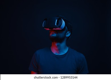 Adult guy in modern VR glasses looking away while standing in dark room and exploring virtual reality