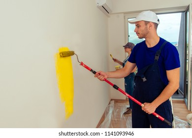 Adult guy painting room yellow with paint stick roller. Young couple decorating an apartment. Renovation concept.