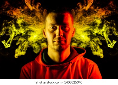 An adult guy stands look forward in hoodie highlighted in yellow and red on the sides with a smile on a black isolated background with pattern of colorful smoke like snakes in the gorgon jellyfish