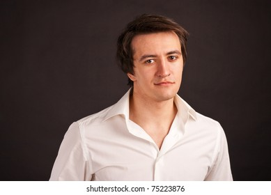 adult guy in a white shirt on black background