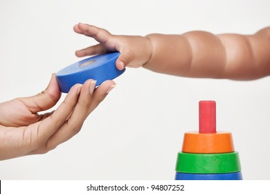 Adult hand gives a building block and baby learns to grip it