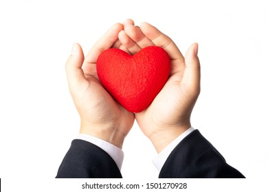 An adult hand holding a red heart on a white background.