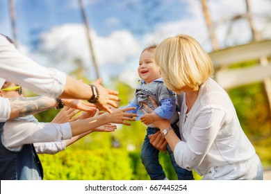A lot of adult hands are drawn to a one-year-old kid, whom Mom holds in his arms. Baby laughs with delight
