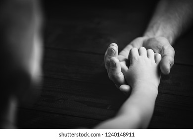 Adult hands holding kid hands, Family Help Care Concept, small hands in fathers hand..black and white.