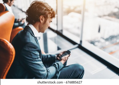 Adult handsome bearded businessman messaging via his smartphone with his colleagues, man entrepreneur in formal suite chatting on cellphone while sitting on armchair next to skyscraper office window