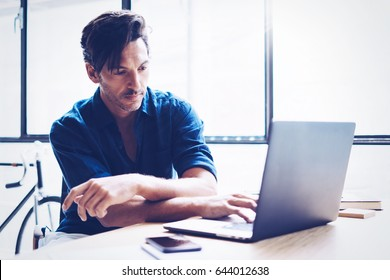 Adult handsome businessman working contemporary notebook while sitting at the wooden table at sunny office.Blurred background. Horizontal.