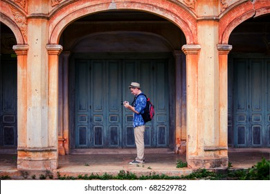 An adult handsome man touring inancient architecture French style village in Tharae Sakon Nakhon Landmark ancient of French in Thailand.Adult handsome man tourism
