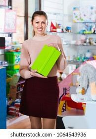 Adult happy cheerful positive smiling woman consumer with color box among children's toys in the store