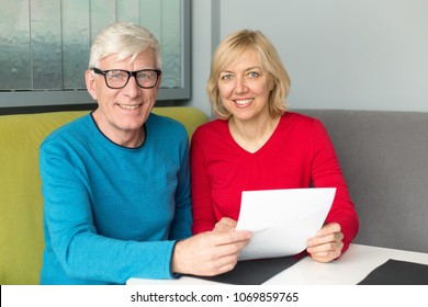 Adult happy couple make out papers sitting at a table. To sign a pension insurance policy or contract.