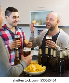 Adult happy men relaxing with beer and smiling at home
