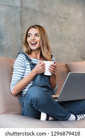 adult happy woman sitting with cup and laptop on pink sofa