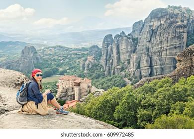 Adult happy woman traveler enjoys  landscape with volcanic mountains.  Meteora monasteries, Greece.