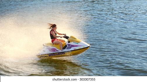 カリフォルニア海洋で、黄色と白のジェットスキーに乗って波を飛ばす楽しみを持つ大人