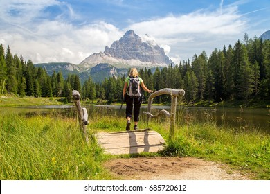 Adult hiker on a wooden bridge across the lake Antorno, in the background tops of Tre cime di Lavaredo, Dolomiti, Italy
