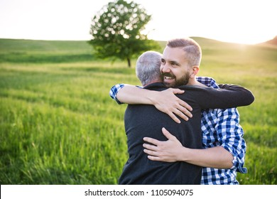 An adult hipster son with senior father on a walk in nature at sunset, hugging.