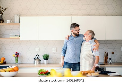 Adult hipster son and senior father indoors in kitchen at home, talking.