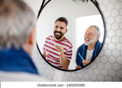 An adult hipster son and senior father in bathroom indoors at home, brushing teeth.