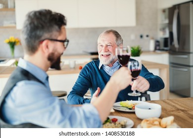An adult hipster son and senior father indoors at home, eating light lunch.