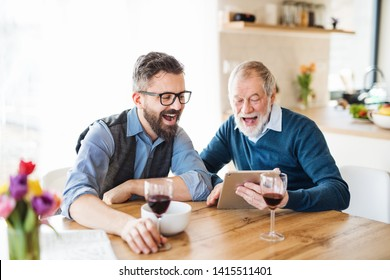 Adult hipster son and senior father sitting at the table indoors at home.