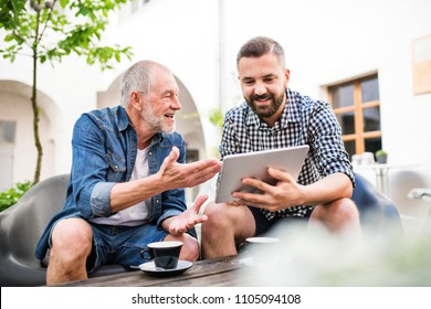 An adult hipster son with tablet and senior father in a cafe in town.