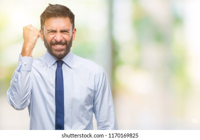 Adult hispanic business man over isolated background angry and mad raising fist frustrated and furious while shouting with anger. Rage and aggressive concept.