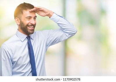 Adult hispanic business man over isolated background very happy and smiling looking far away with hand over head. Searching concept.