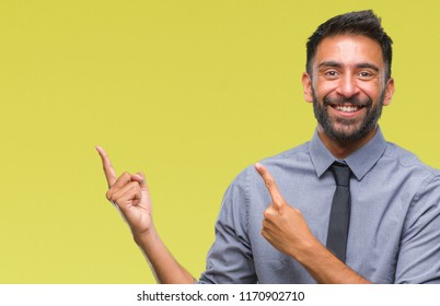 Adult hispanic business man over isolated background smiling and looking at the camera pointing with two hands and fingers to the side.