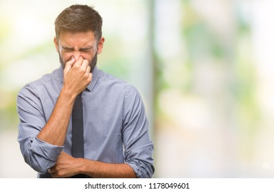Adult hispanic business man over isolated background smelling something stinky and disgusting, intolerable smell, holding breath with fingers on nose. Bad smells concept.
