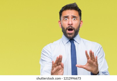 Adult hispanic business man over isolated background afraid and terrified with fear expression stop gesture with hands, shouting in shock. Panic concept.