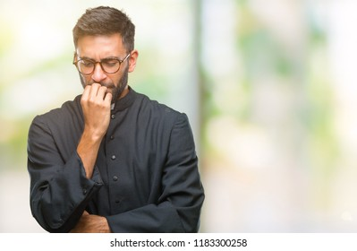 Adult hispanic catholic priest man over isolated background looking stressed and nervous with hands on mouth biting nails. Anxiety problem.