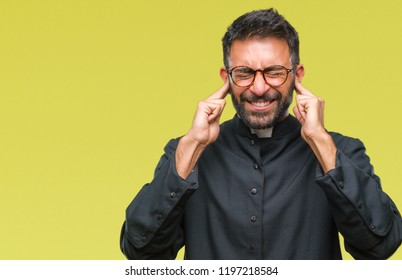 Adult hispanic catholic priest man over isolated background covering ears with fingers with annoyed expression for the noise of loud music. Deaf concept.